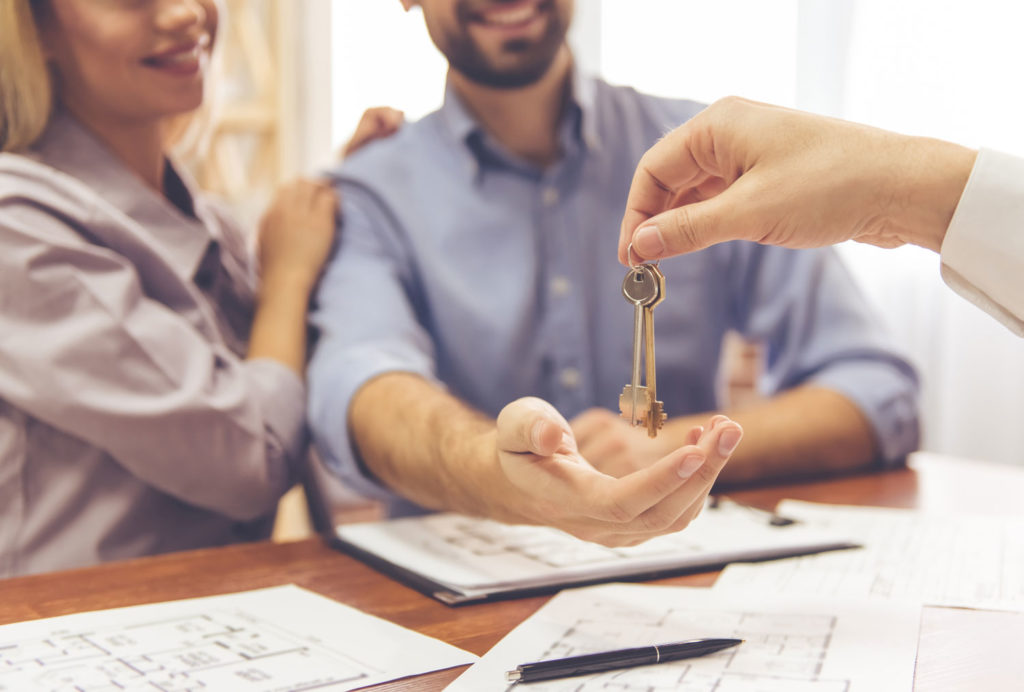 Real estate agent handing homebuyers their new house keys.