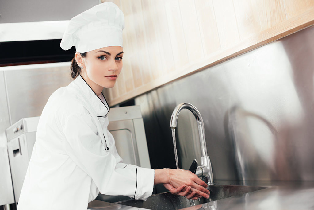 Kitchen worker washes her hands properly. Food service industry. Proper hand washing.