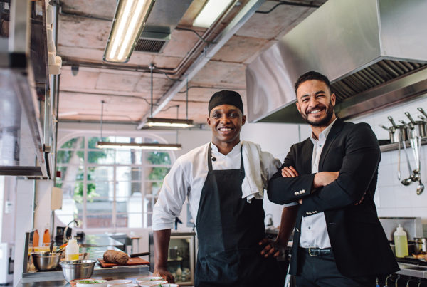 Employer and employee stand in kitchen happy. Food service industry.