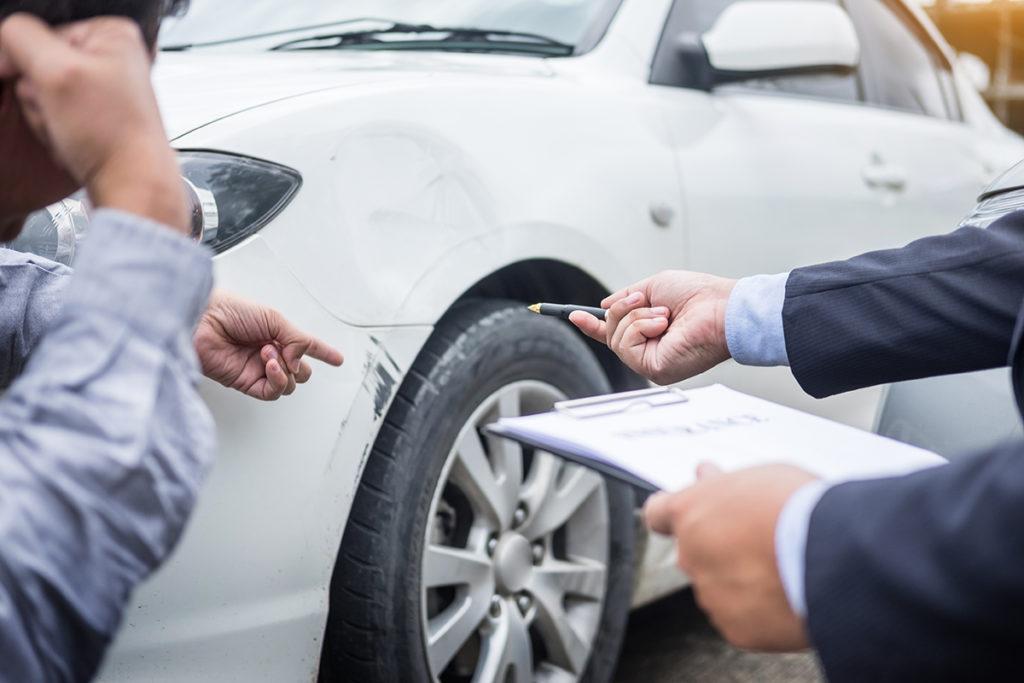 Insurance Adjuster. Insurance Training. Insurance agent looking at damaged car