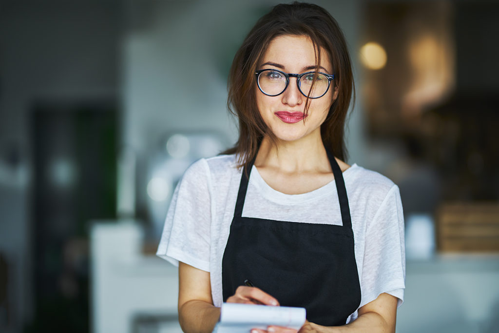 make more tips. A server with messy hair and glasses writes down a customers order on a notepad.